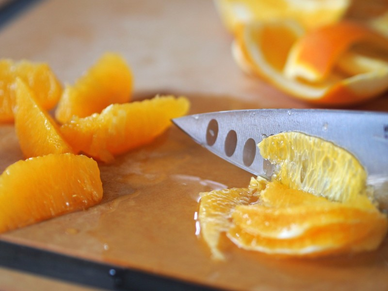 Removing just the flesh from an orange.